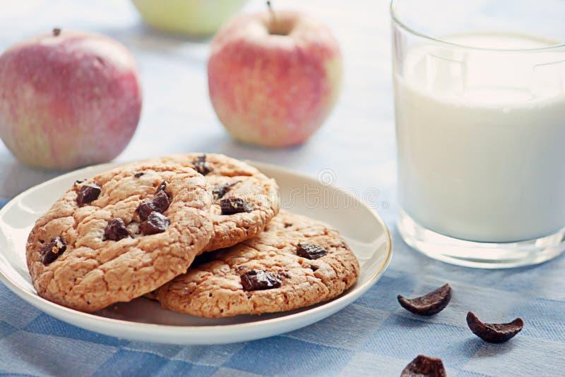Desayuno delicioso: leche, galletas y manzanas imagen de archivo