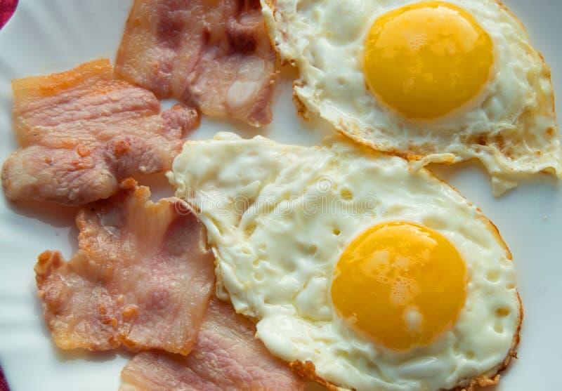 Desayuno delicioso - placa blanca de huevos fritos, tocino imagen de archivo