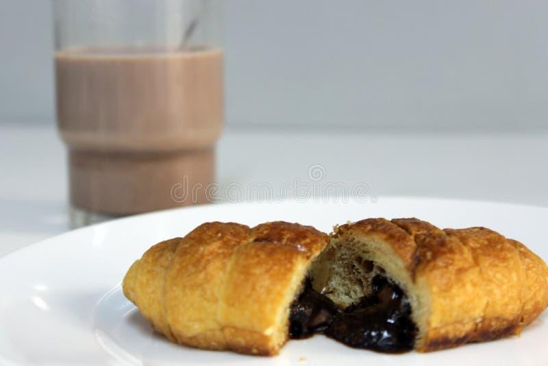 Desayuno delicioso que consiste en un cruasán del chocolate y un vidrio de leche con cacao foto de archivo