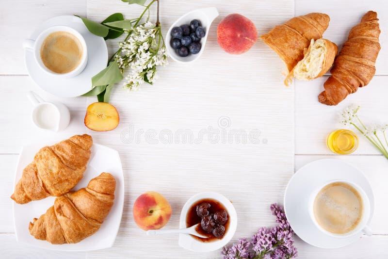 Desayuno - dos tazas de café, de cruasanes, de atasco, de miel y de frutas en la tabla blanca imágenes de archivo libres de regalías