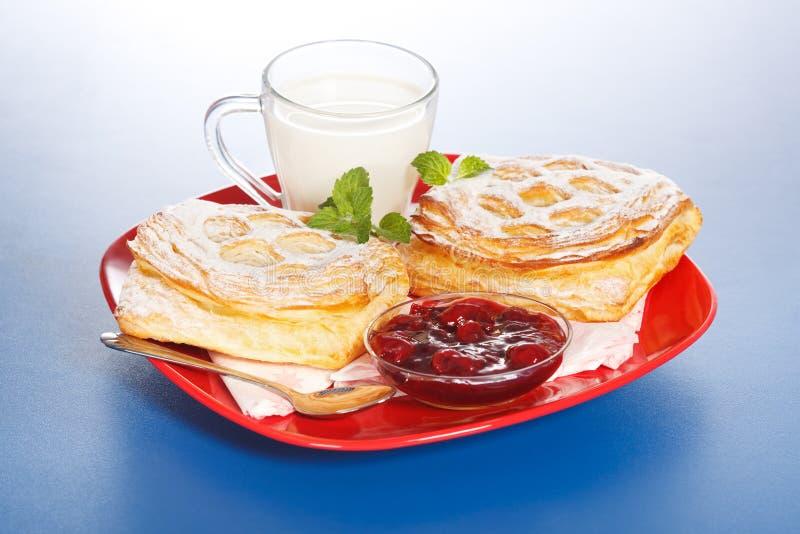 Desayuno: dos tortas, leche y atasco de la cereza amarga en la placa foto de archivo