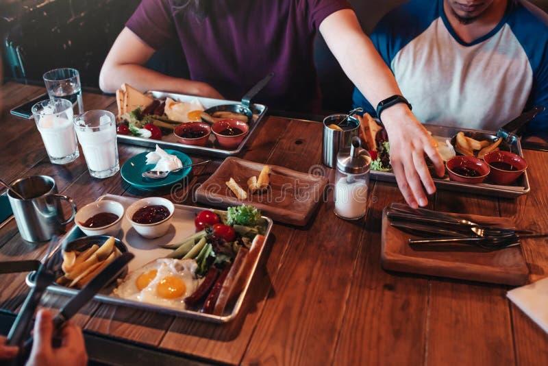 Desayuno en café Los amigos comen el desayuno en café Los hombres jovenes están a punto de comenzar su comida y bebidas fotos de archivo