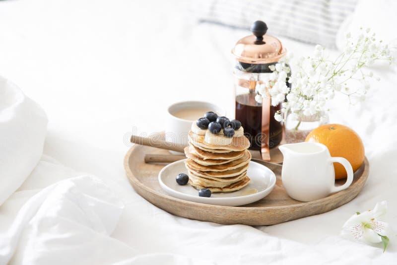 Desayuno en cama Crepes con los ar?ndanos y miel, caf?, leche y naranja fresca servidos en la bandeja de madera en las hojas blan fotos de archivo