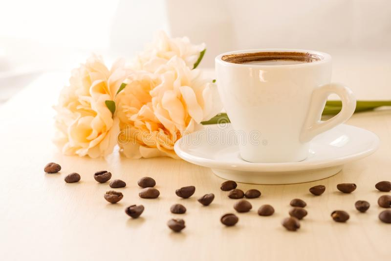 Desayuno en colores en colores pastel Taza de café que se coloca en la tabla con los granos de café dispersados alrededor, cont fotos de archivo