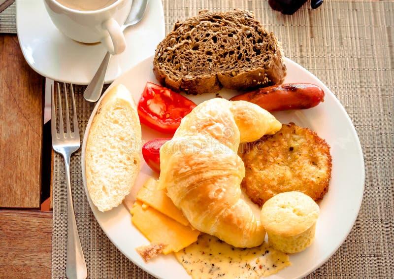 Desayuno en el café con el cruasán, pan, queso, tomates en la placa foto de archivo libre de regalías