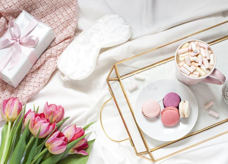 Desayuno en la composición puesta plana en colores pastel de la cama con flores, un café de la taza o y dulces fotos de archivo