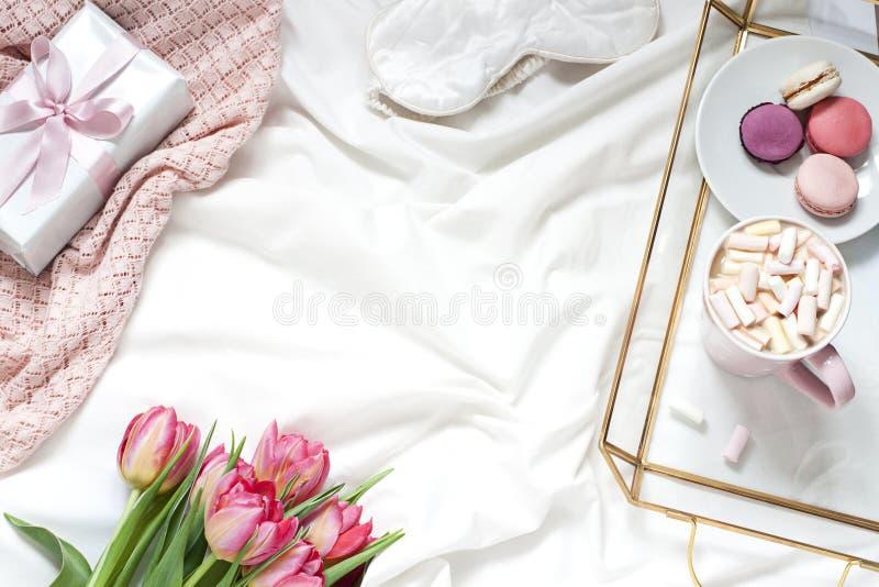 Desayuno en la composición puesta plana en colores pastel de la cama con flores, un café de la taza o y dulces imágenes de archivo libres de regalías