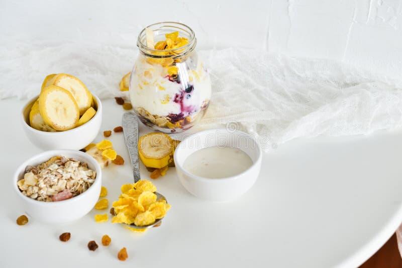 Desayuno en un tarro: copos de maíz, plátano, bayas frescas, granola, yogur en un fondo ligero El concepto de consumición sana, a fotografía de archivo libre de regalías