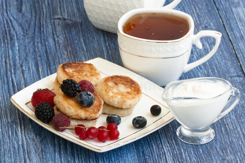 Desayuno gastrónomo - crepes del requesón, syrniki, buñuelos de la cuajada con la frambuesa, fresa, arándano, Blackberry foto de archivo