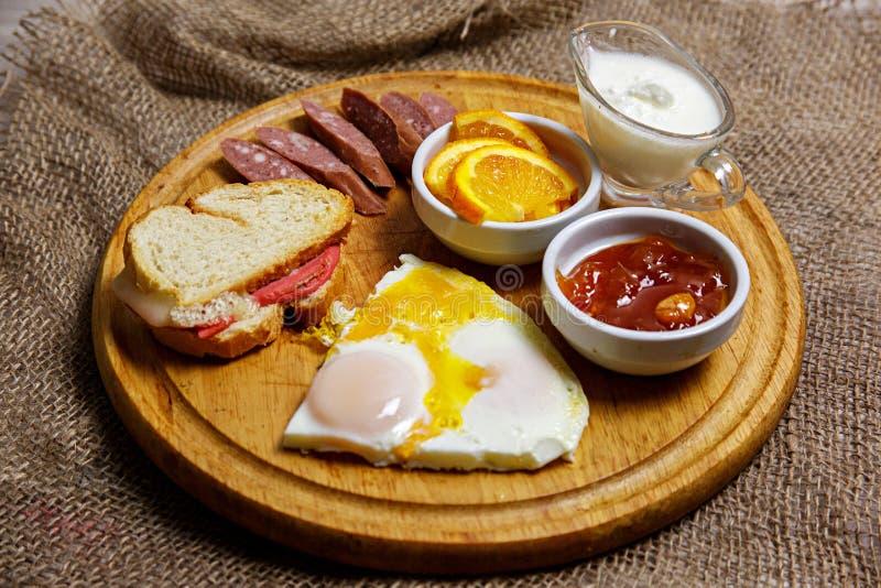Desayuno hecho en casa natural de los huevos revueltos, tostada, salchichas de la caza y atasco, presentados en una placa de made fotografía de archivo