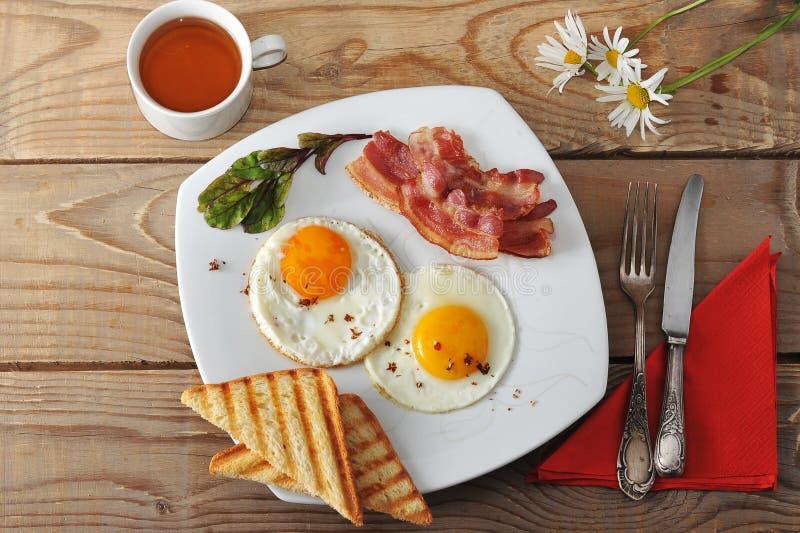 Desayuno - huevos fritos, tostada, tocino y té y manzanilla en el wo imagenes de archivo