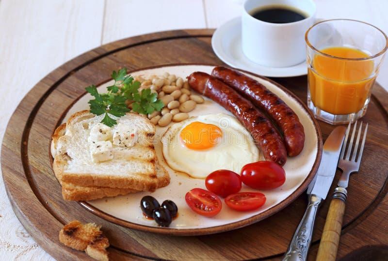 Desayuno inglés con la salchicha, el huevo frito y las habas cocidas fotografía de archivo