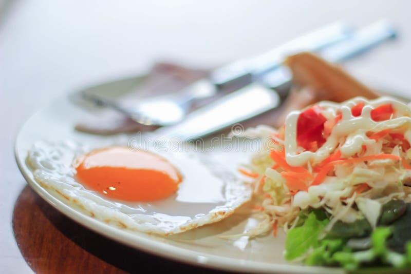 Desayuno inglés con los huevos fritos, tocino, salchichas, habas, tostada foto de archivo