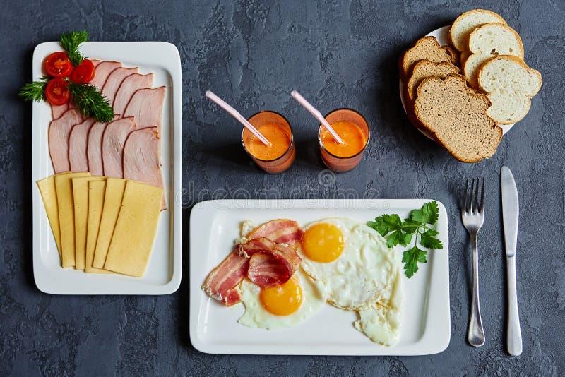 Desayuno inglés con los huevos revueltos y el tocino, jugo de zanahoria, b fotografía de archivo