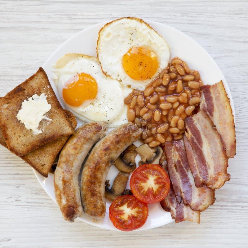 Desayuno inglés lleno con los huevos fritos, las salchichas, las habas, el tocino y las tostadas en un fondo de madera blanco Vis imagen de archivo