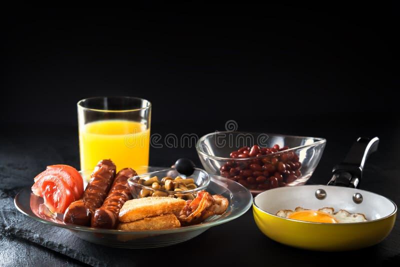Desayuno inglés lleno con los huevos revueltos en un sartén, un tocino, una salchicha, habas, tomates y un jugo imagen de archivo libre de regalías