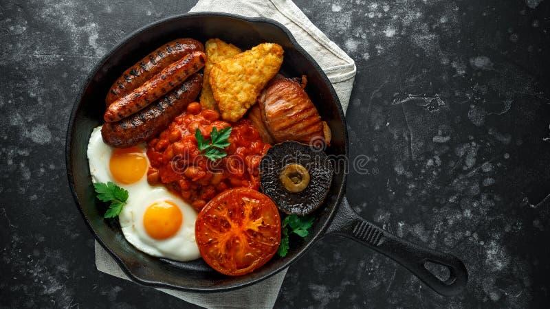 Desayuno inglés lleno con tocino, la salchicha, el huevo frito, las habas cocidas, las papitas fritas y las setas en la sartén rú fotos de archivo libres de regalías