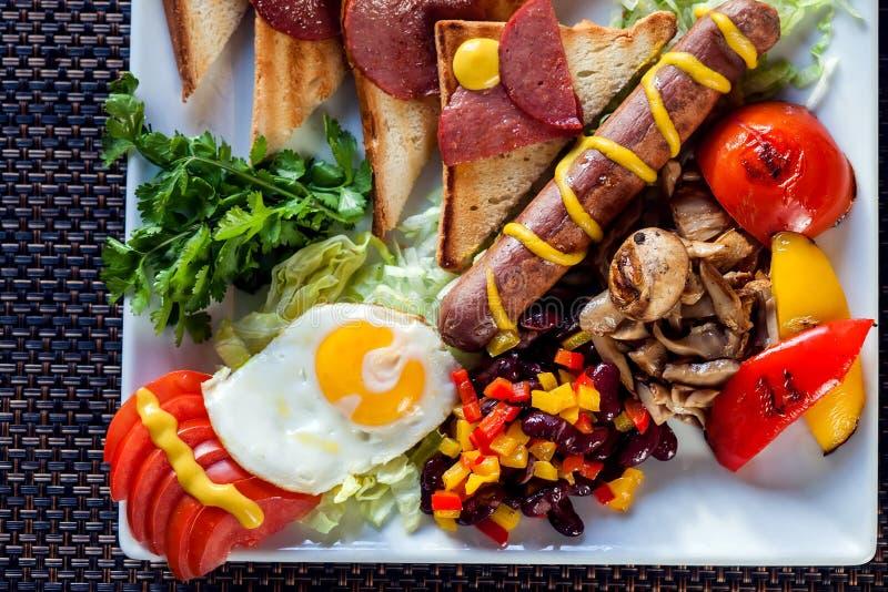Desayuno inglés lleno incluyendo las salchichas, tomates y setas asadas a la parrilla, huevo, tocino, habas cocidas y pan Comida  foto de archivo