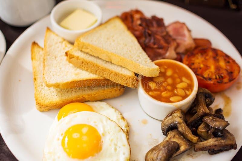 Desayuno inglés lleno tradicional con los huevos fritos del soleado-lado-para arriba, tocino, salchichas, habas en salsa de tomat imagenes de archivo