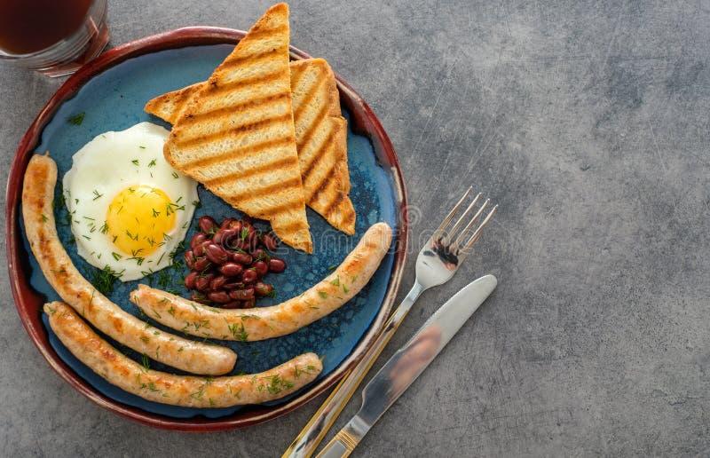 Desayuno inglés lleno tradicional con los huevos fritos, salchichas y fotografía de archivo