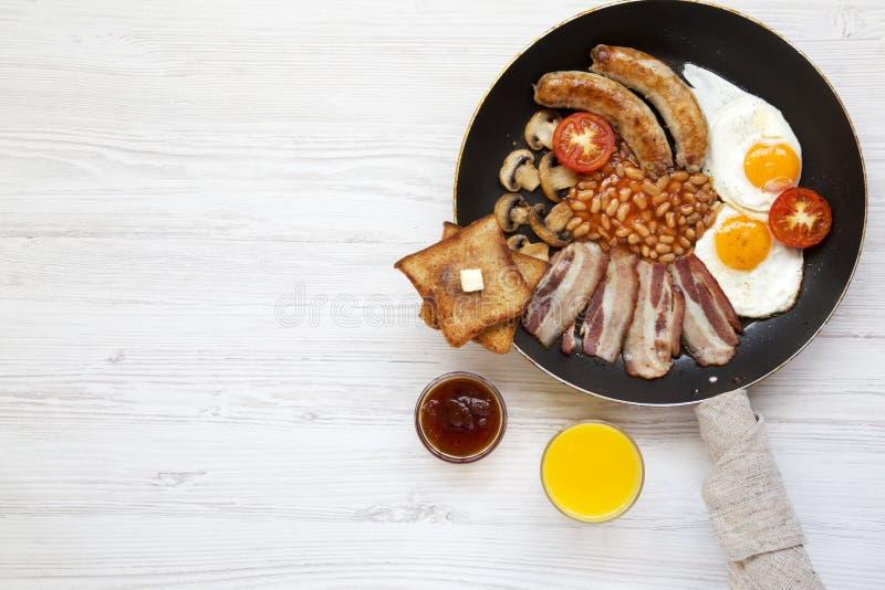 Desayuno inglés lleno tradicional en una cacerola con los huevos fritos, el tocino, las salchichas, las habas, las tostadas y el  fotos de archivo