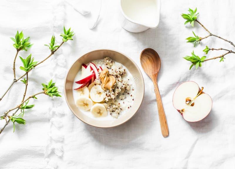 Desayuno libre del gluten - quinoa, leche de coco, plátano, manzana, cuenco de la mantequilla de cacahuete en el fondo ligero, vi imagenes de archivo