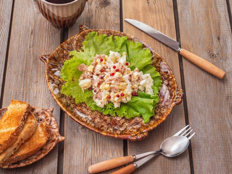 Desayuno ligero con la ensalada de atún y los huevos hervidos en la placa de cerámica decorativa fotografía de archivo