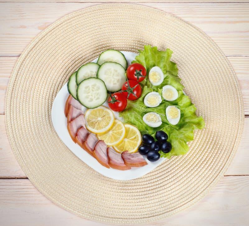 Desayuno ligero de los huevos de codornices, de la lechuga, de los tomates de cereza, del jamón, del limón y de aceitunas en un f fotos de archivo libres de regalías