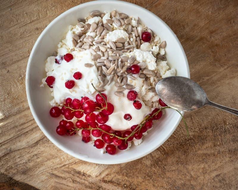 Desayuno ligero y sabroso con requesón, las semillas y el atasco hechos en casa de la baya en una placa profunda blanca con una c imágenes de archivo libres de regalías