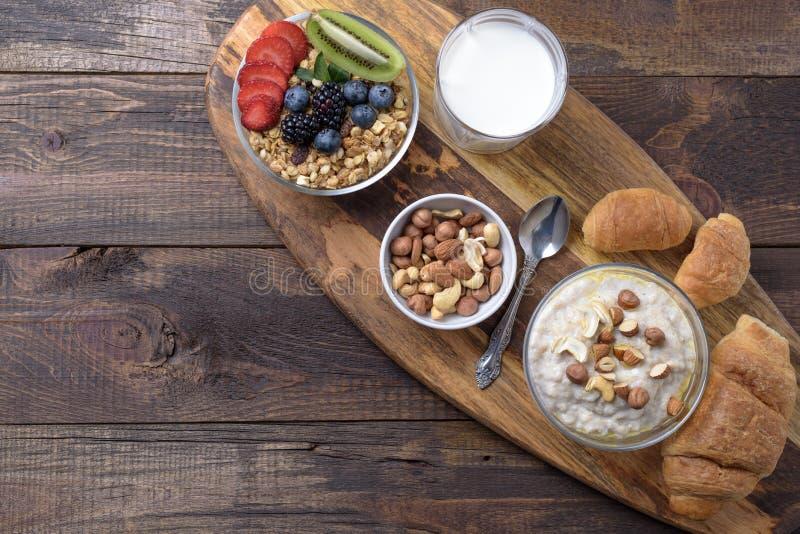Desayuno lleno de la harina de avena con las nueces, del muesli con las bayas y las frutas, de cruasanes y del vidrio de leche en imagen de archivo