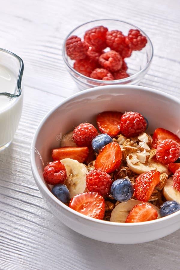 Desayuno natural hecho en casa con el granola, fresas, almendras, arándanos, frambuesa, leche de soja fresca en un cuenco en a fotografía de archivo libre de regalías