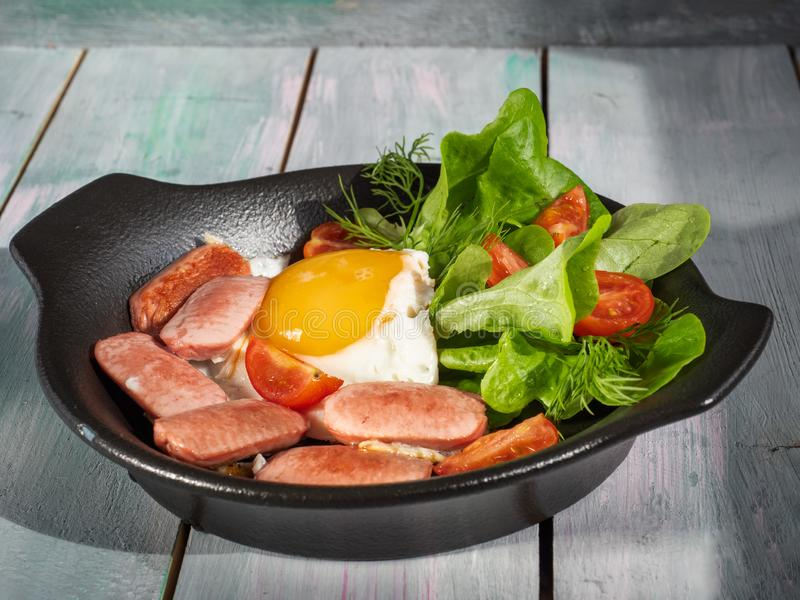 Desayuno nutritivo de huevos fritos con las salchichas, los tomates y la lechuga de hoja en un sartén negro Servicio en una bande imagen de archivo libre de regalías