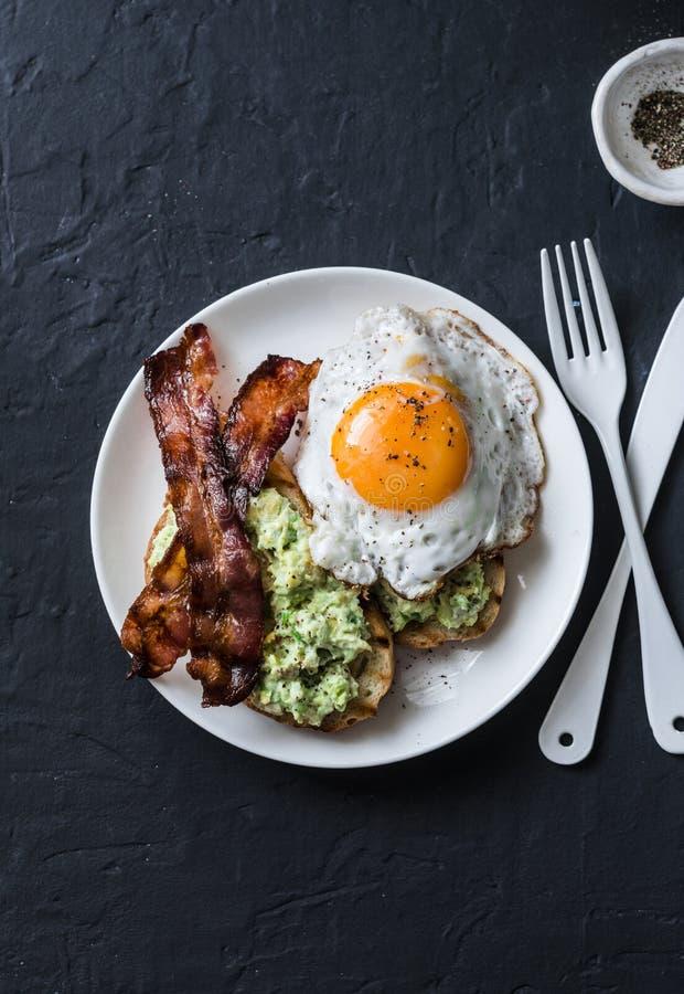 Desayuno nutritivo sano - tostada del aguacate, tocino y huevo frito en fondo oscuro fotografía de archivo libre de regalías