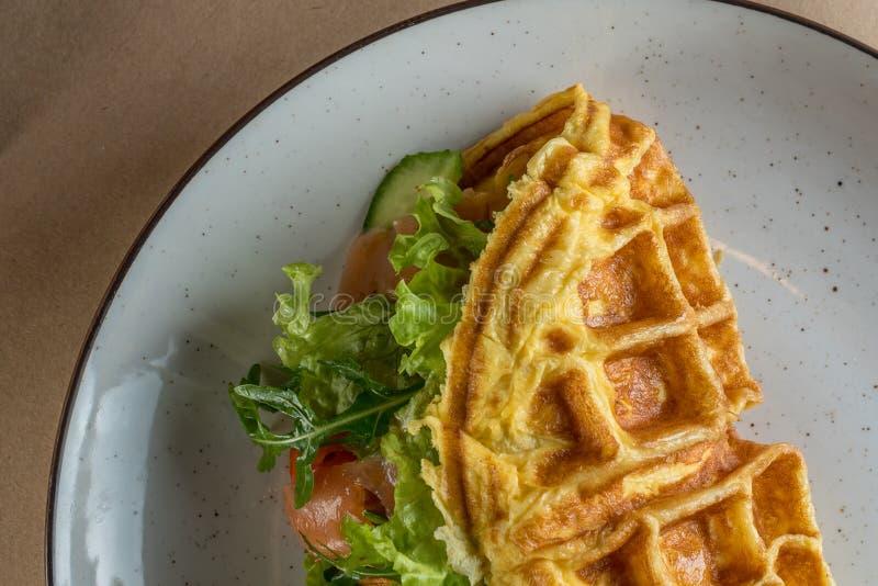 Desayuno nutritivo y sano - tortilla con las verduras, con las hojas de la ensalada y los pescados rojos - salmones r foto de archivo