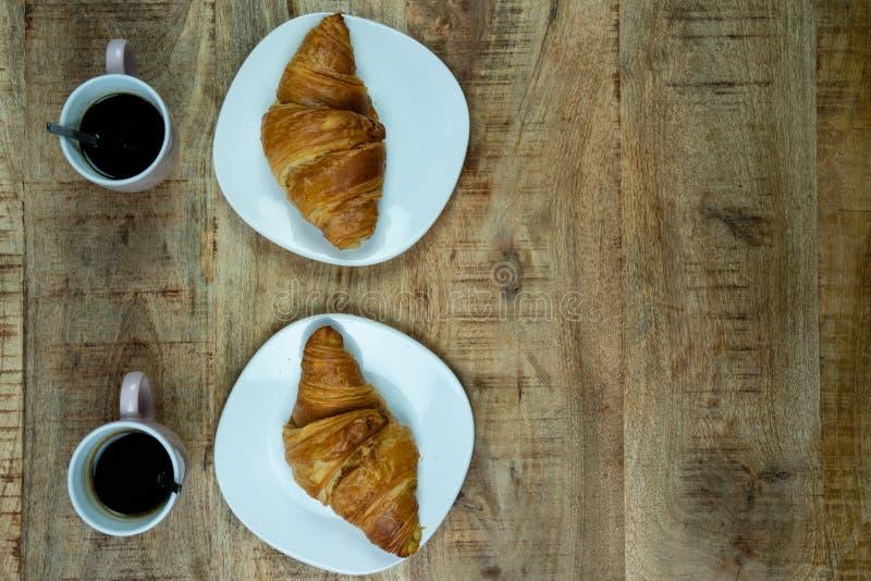 Desayuno o almuerzo para dos Cruasanes en una placa con café fotografía de archivo libre de regalías