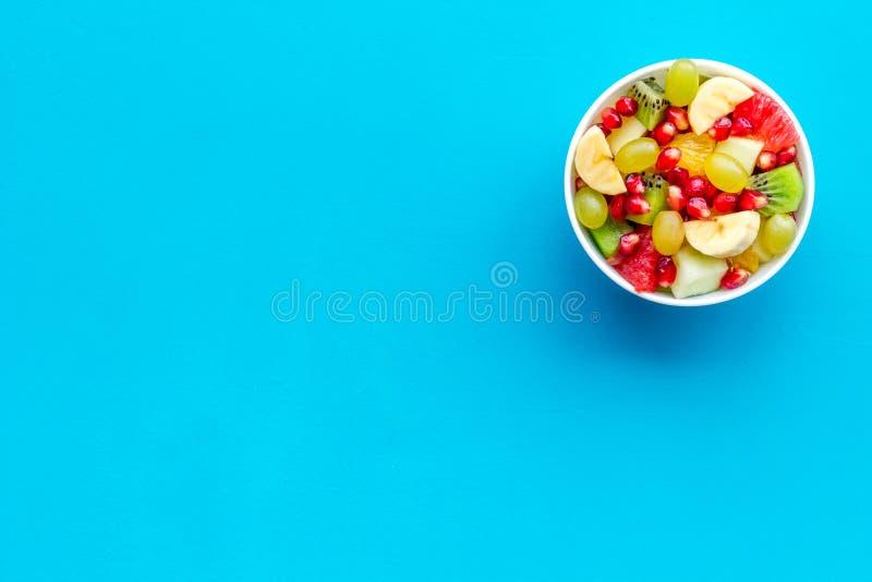 Desayuno o aperitivo sano ligero Ensalada de fruta con la manzana, el kiwi y la granada en cuenco en la opinión superior del fond imagen de archivo