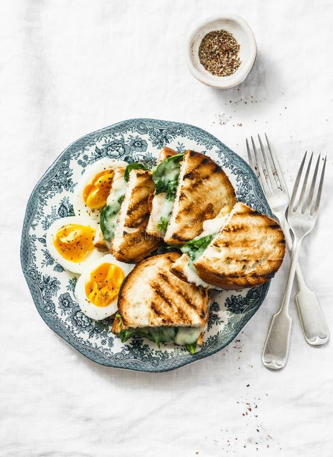 Desayuno o bocado sano - la granja hervida eggs, la espinaca, bocadillos asados a la parrilla del queso en fondo ligero imagen de archivo