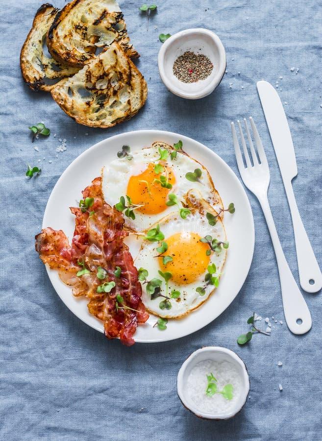 Desayuno o bocado tradicional - los huevos fritos, tocino, asaron a la parrilla el pan en el fondo azul, visión superior imagenes de archivo
