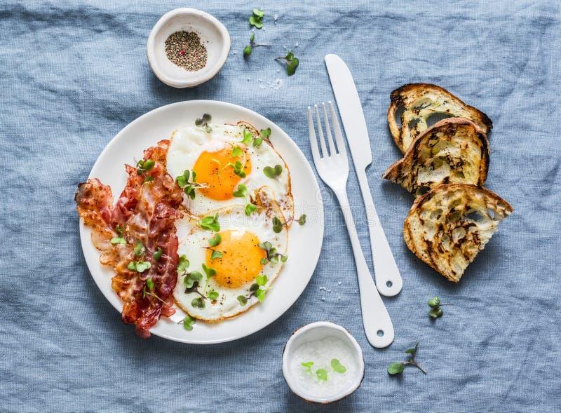 Desayuno o bocado tradicional - los huevos fritos, tocino, asaron a la parrilla el pan en el fondo azul, visión superior imagen de archivo