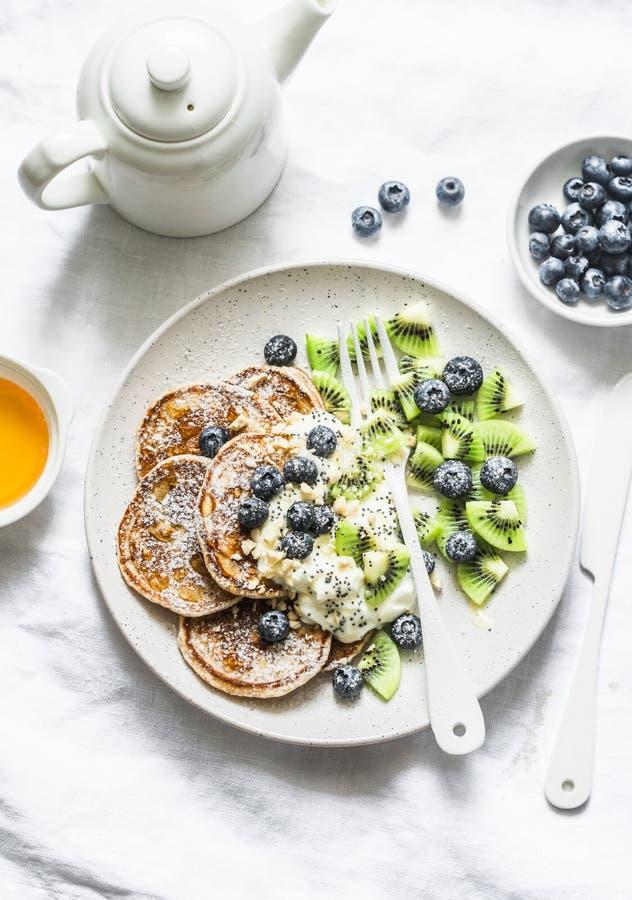 Desayuno o postre servido - crepes del trigo integral con el yogur, los arándanos, el kiwi, la miel y las nueces griegos en un fo fotos de archivo libres de regalías
