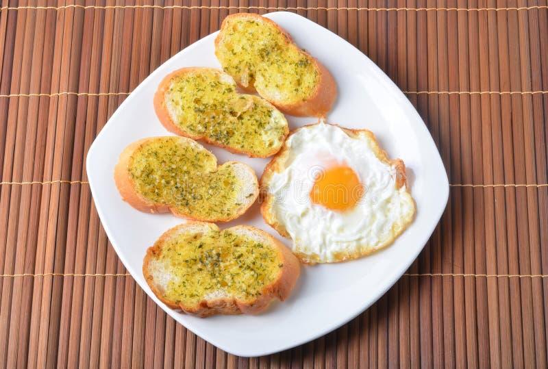 Desayuno, pan de ajo, huevo frito fotos de archivo
