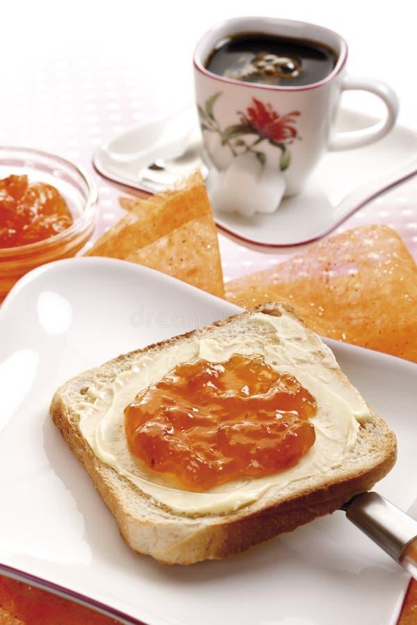 Desayuno, parte de la tostada con mantequilla y atasco anaranjado fotografía de archivo libre de regalías