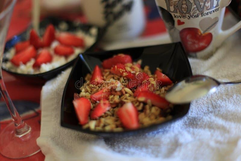 Desayuno perfecto: granola crujiente con el yogur y las fresas con una taza de café de la leche en la tabla de mármol Buenos días fotografía de archivo libre de regalías