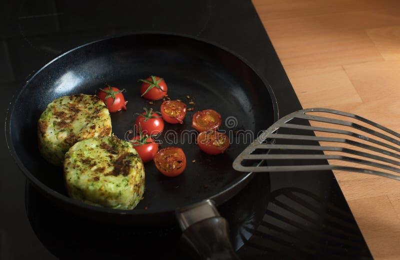 Desayuno que cocina con el tomate y la patata en la cacerola fotografía de archivo libre de regalías