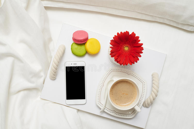Desayuno romántico con café, los macarrones y el teléfono móvil en el tr imagenes de archivo
