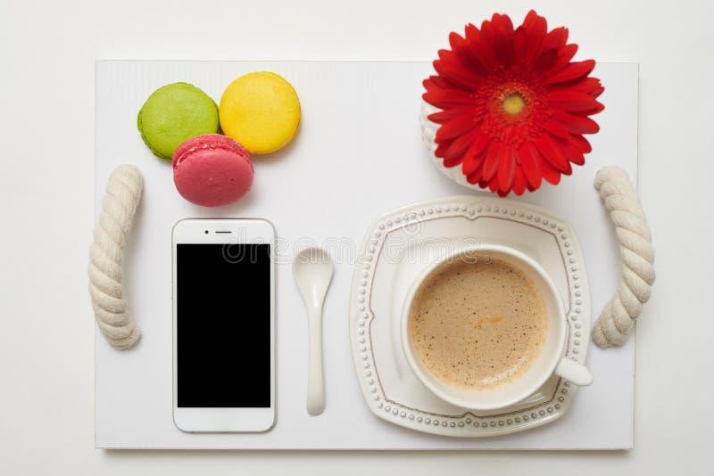 Desayuno romántico con café, los macarrones y el teléfono móvil en el tr imágenes de archivo libres de regalías