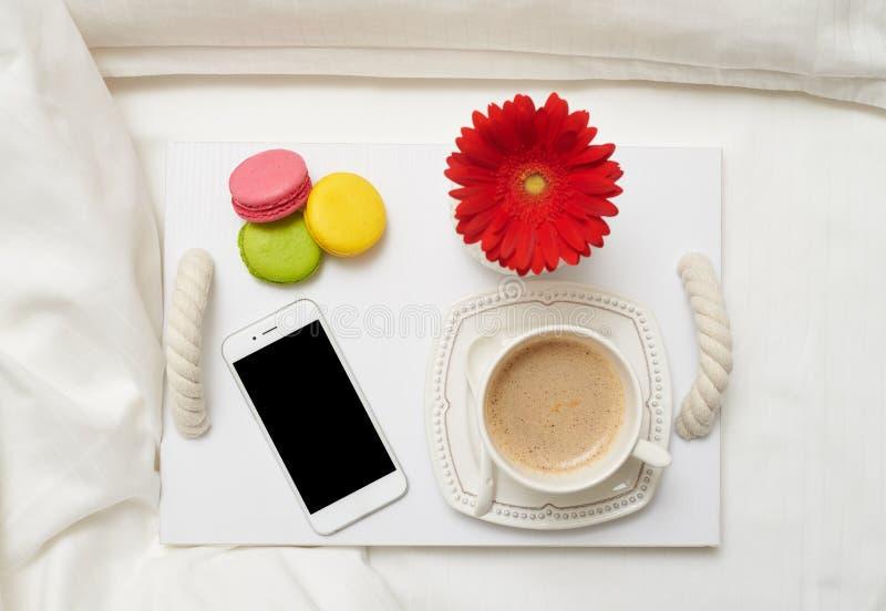 Desayuno romántico con café, los macarrones y el teléfono móvil en el tr foto de archivo
