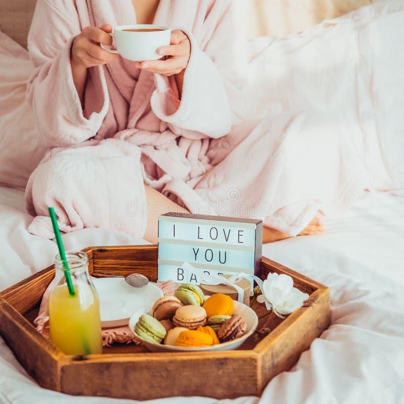 Desayuno romántico en cama con te amo el texto en la caja encendida, los macarrones, la caja de regalo en la bandeja de madera y  imagen de archivo libre de regalías