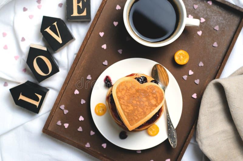 Desayuno romántico en la cama, crepes, café, letras de amor en la sábana blanca imagen de archivo libre de regalías