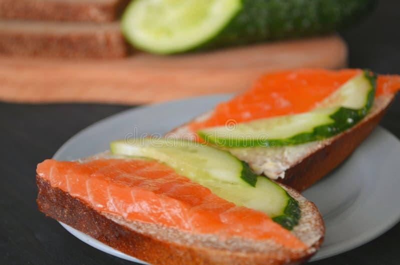 Desayuno sándwich sano con salmón y pepino, pan marrón y mantequilla sobre un fondo de madera foto de archivo